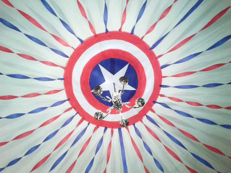 Paper Captain America sheild on the ceiling with crepe paper streamers for superhero party decoration