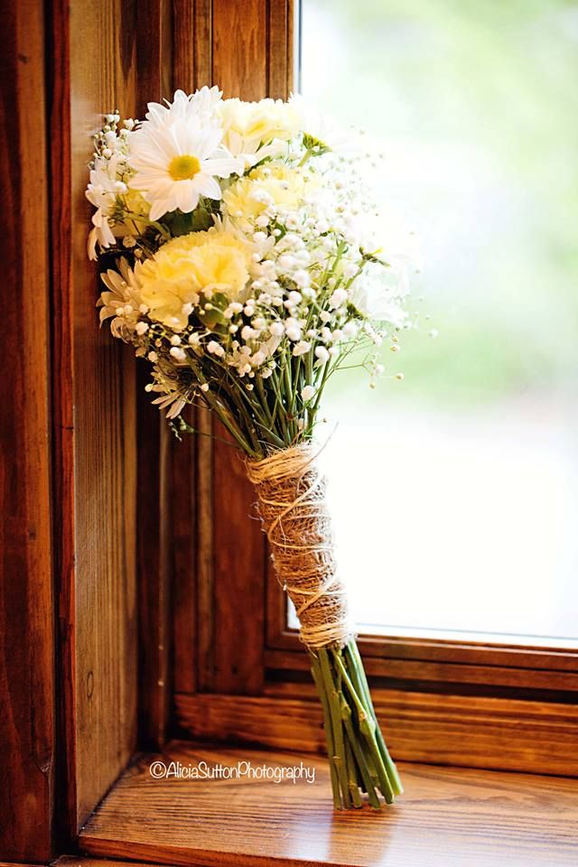 Bride's maid's hand tied bouquet of Pale yellow carnations, baby's breath and white daisies.  Tied with burlap and twine.