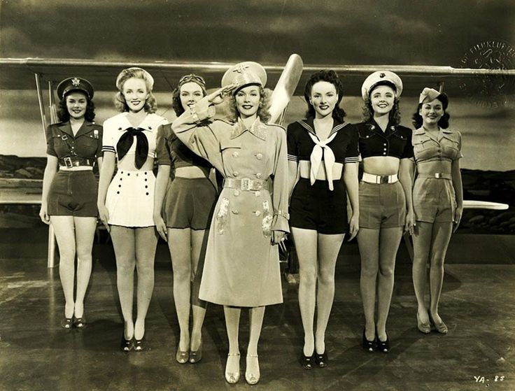 Still photo of WWII pinup girls from the 1941 movie 'You're In The Army Now.' The lady in the center is Jane Wyman (Ronald Regan's first wife of 10 years).  They represent all the armed services. From left to right: Army, Navy, U.S. Army Air Corp, KGB Spy, Coast Guard, Marines, and National Guard.