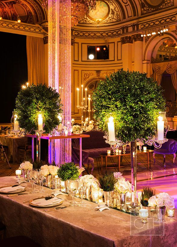 For this lavish wedding each table was exquisitely designed to compliment the next and highlighted everything from faux fur chair covers to candelabras that gave the appearance of lush green trees.