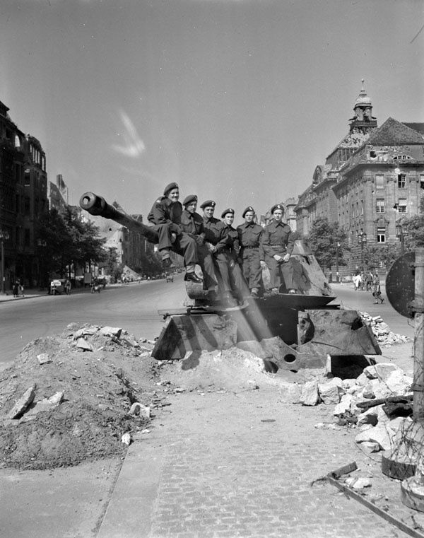 Personnel of the Canadian Berlin Battalion sitting on a dug-in German tank, Berlin, Germany, 14 July 1945.