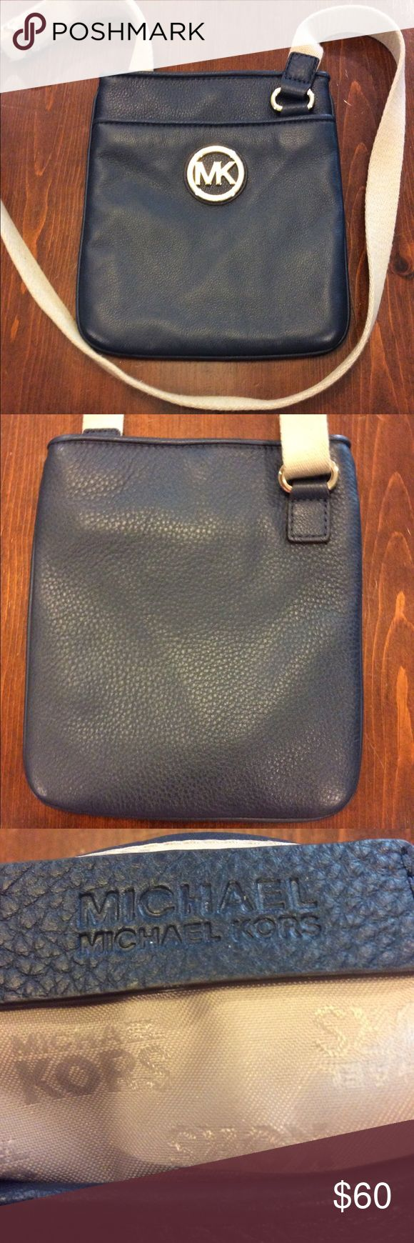 """Michael Kors Navy Jet Set crossbody handbag Michael Kors navy jet set crossbody handbag in excellent condition. Navy pebble leather with gold MK Circle medallion on front of bag. Height 9"""", width 8"""". Adjustable khaki canvas strap. Front outside pocket; two interior pockets. MICHAEL Michael Kors Bags Crossbody Bags"""