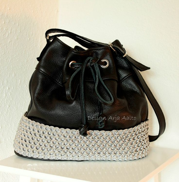 Leather handbag with soda can tabs.