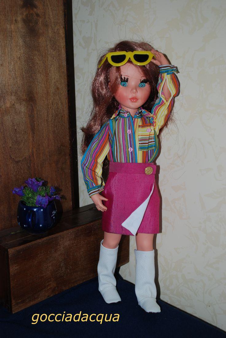 Sheila in un repro di 'Lungo Senna' 1968 con la camicia a righe multicolori e la gonna rosa ciclamino a portafoglio. Stivali in pelle bianca