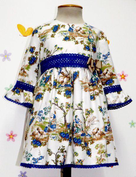 Vestido para bebe niña de toilé en tonos azules y manga francesa, adornado con encaje de bolillos y lazo camel a juego. Talle alto.