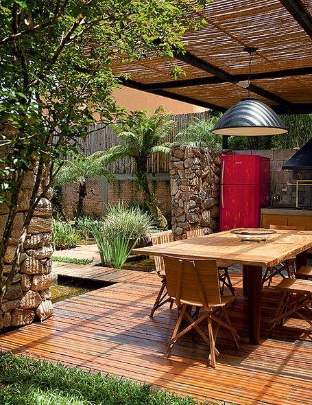 Na área gourmet, a pérgola tem cobertura de vidro temperado. Debaixo dele, réguas de bambu promovem um bonito e delicioso sombreado para cur...