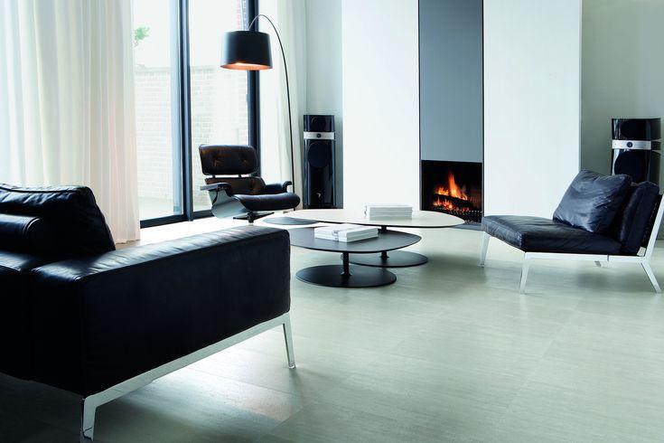 Gebroken wit voor de muren en een lichtgrijze vloer geven de kamer een luchtige en ruime uitstraling. #kurk #vloer #design #woonkamer