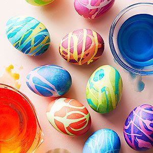 Drizzle the shells of boiled eggs with rubber cement; let dry; dip in dye; let dry; gently peel off rubber cement; dip in again in dye one to three times.