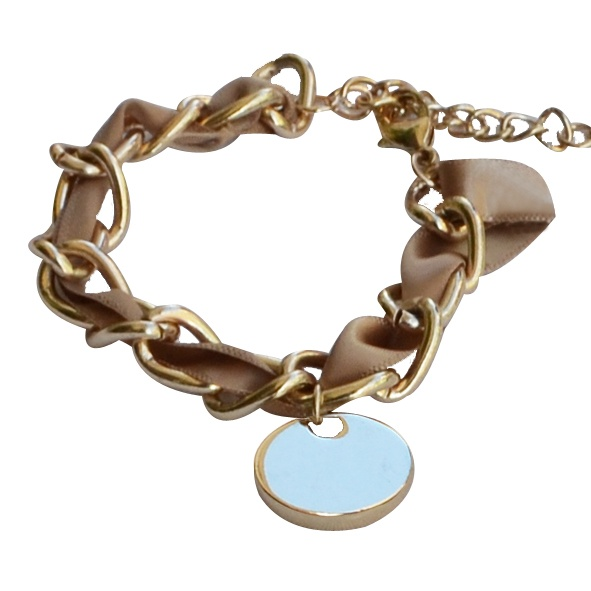 Vintage charm in beige     Gold color faux chain bracelet , with beige satin ribbon. There is a round charm hanging.