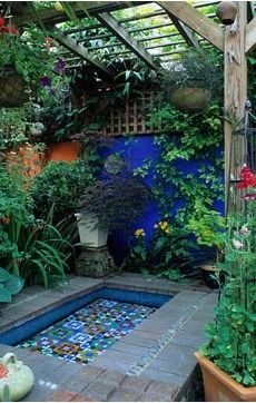 Moroccan style garden with blue painted wall, mosaic pool, brick paviors, Brighton, Sussex