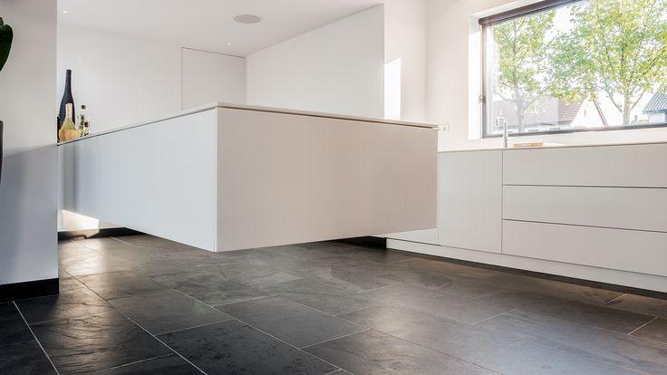 Zwevend Himacs keukenblad met lage keukenkasten/aanrecht aan voorgevel. Zowel het keukenblad als de keukenkastjes zijn van 12mm wit Himacs gemaakt.