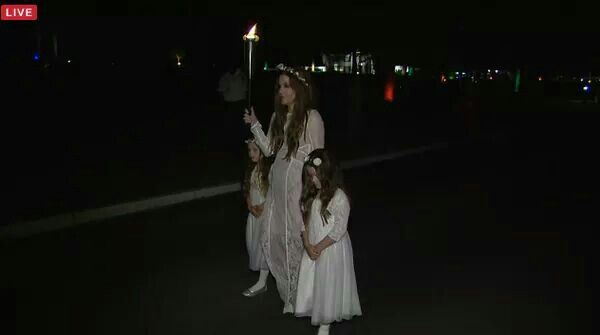 2015 August 16th Lisa Presley & her twin daughter's walking from the meditation garden at Graceland where Elvis is buried walking with a candle dwn to the gates ov Graceland to let the fans threw the gates an to lite there candles... You can see Graceland house lights in the background...