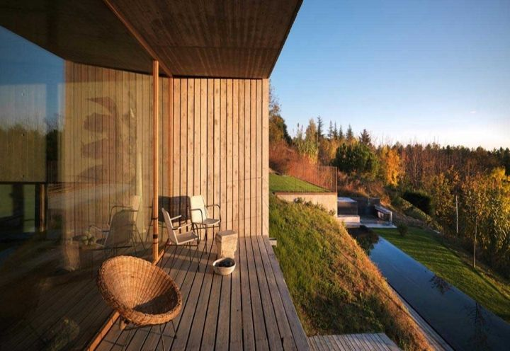 La zona living di House Y prosegue all'aperto, con un loggiato in doghe di legno che guarda alle colline del Torinese e alla piscina mimetizzata nel verde