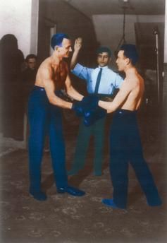 George Grosz, Wieland Herzfelde and John Heartfield during boxing training, Erwin Piscator in the background.  Berli, c. 1924. Photo, coloured later.