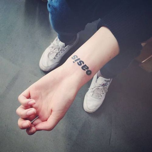 Logo of Oasis music band on the wrist. Tattoo artist: Doy