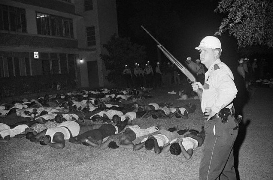 Original Caption:  Houston -- A police officer guards some of the 500 students at Texas Southern University - an historically Black college - arrested during a riot where a policeman was killed and three others wounded. Officers claim that shots were fired at them from a dormitory window after a rally on campus became violent. (1967)