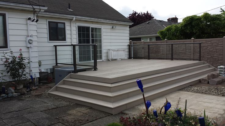 This is an amazing example of a durable and beautiful PVC deck, an aluminum handrail with glass inserts to keep the space open, and off in the back we can see some gorgeous EcoStone fencing. I love that they kept the deck mostly open with stairs down to the rest of the yard.
