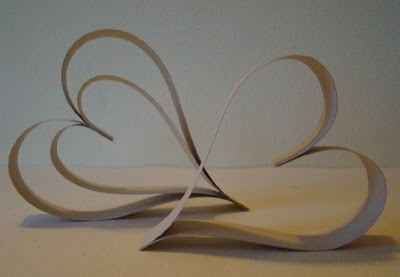 Cut two 12-inch strips and two 9 1/2-inch strips. Line them up in this order: 9 1/2, 12, 12, 9 1/2, with one set of ends even. Staple this end. Now bend the unstapled ends into a heart shape, so a small heart lies inside a larger heart. Align the ends and staple together. (I put this on top of a gift for Brian ~ Amber)