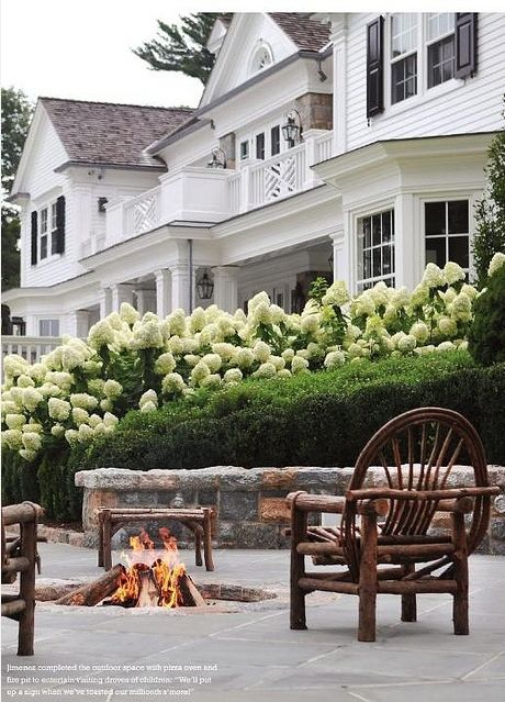 """White exterior paint, brick red porches, Black exterior paint on some small areas.  And for SOME of the yard, nicely trimmed up Boxwood hedges, and lovely hydrangeas."" I just really liked the fire pit lol :):"