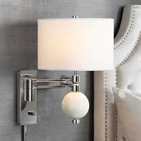 A stylish West Highland White glass ball accent adds a wonderful pop of color to this chrome finish swing arm wall lamp.