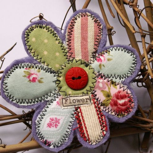 Flower Brooch backed with wool felt and collaged with a colourful patchwork of cottons. Finished with a red button.