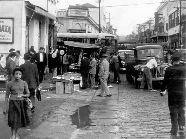 Década de 50 - Rua 12 de Outubro, bairro da Lapa. A esquerda onde temos o ônibus é a rua Cincinato Pomponet. A esquerda temos parte de uma placa com anúncio de filme em cartaz no Cine Tropical. O prédio a direita é o Cine Carlos Gomes.