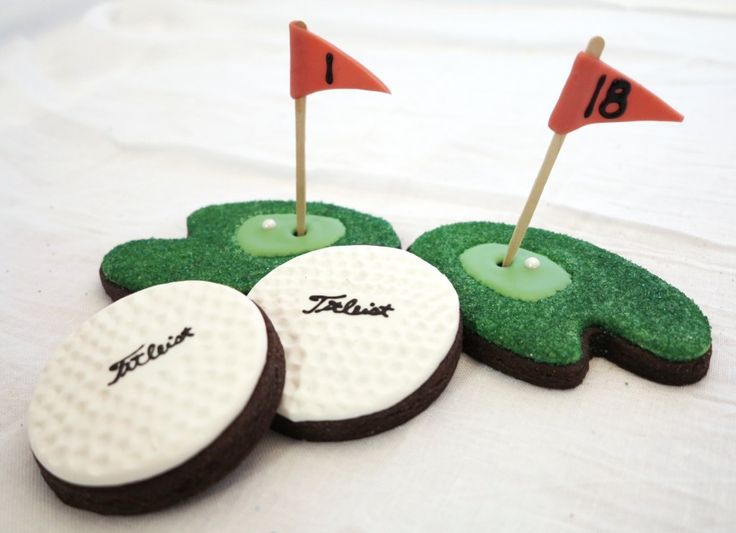 flags? warmed up a red Tootsie Roll, used a fondant roller to flatten, cut shape with a knife, added the numbers with black glaze and wrapped it around a large toothpick. FYI, regular Tootsie Rolls are awesome for cookie decorating! I used a paint palette cutter for the putting green while  cookies till warm I used the end of a straw to cut out the hole. the golf balls were covered with white glaze-allowed to dry 45-60 minutes I gently pressed surface with the rounded end of a small paint…