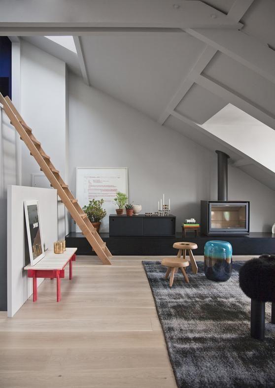 Sotto i tetti di Parigi Una vista della scala che porta al mezzanino, dove si trova l'alloggio per gli ospiti. La panca in legno bicolore è 'Heights', disegnata da Alban le Henry per Great Design. Il tappeto si trova a Milano da Mohebban.
