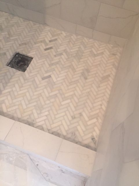 From hellolovely.com, an in-progress shower tiled in a Carrara marble herringbone.