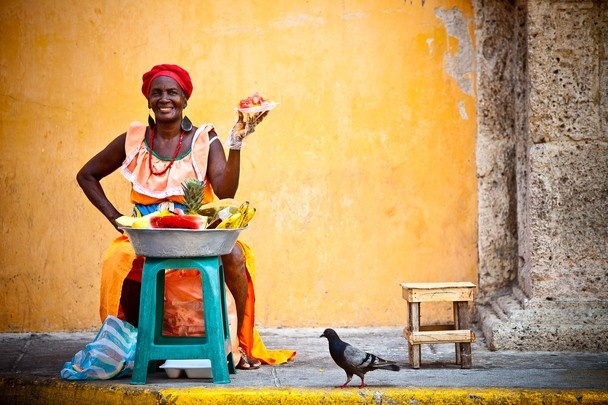 Street shot of a lady selling fruit in Plaza Santo Domingo, Cartagena, Colombia.