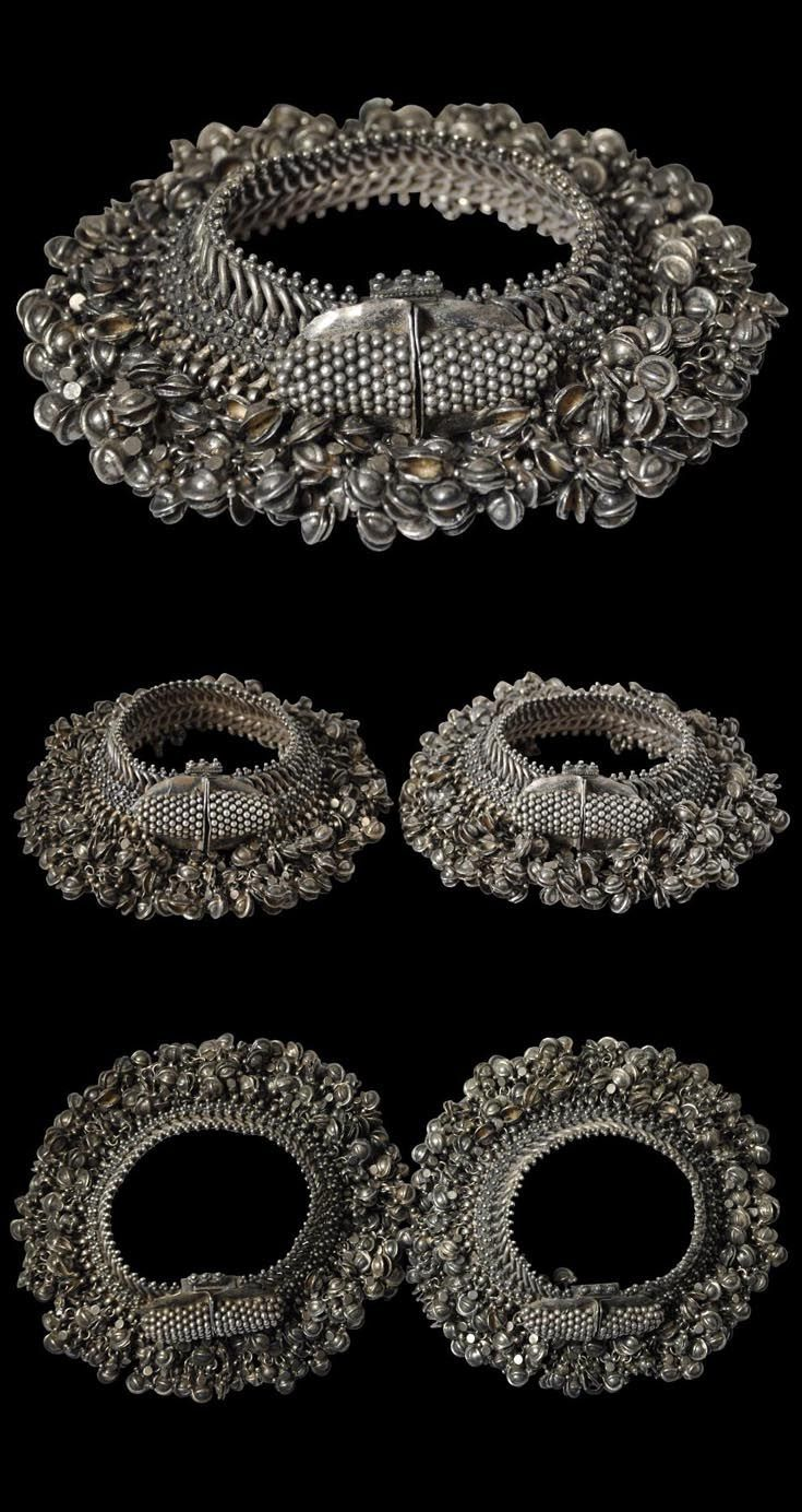 India - Rajasthan | Pair of anklets; flexible silver alloy anklets open and close with a pin mechanism. They comprise a woven silver wire sub-structure to which attached are dozens of small silver flower motifs and many dozens of bell-like pendants cast in the shape of open seed pods. These knock against each other when the wearer moves to generate a pleasing 'shimmering' sound | ca. early 20th century | Sold: