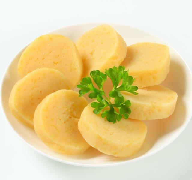 bramborové knedlíky  1 kg brambor 2 vejce lžíce mléka cca 400 g hrubé mouky 3 lžíce hrubé dětské krupičky sůl Brambory, den předem vařené ve slupce, oloupeme, nastrouháme na hrubém okurkovém struhadle, v míse je osolíme a smícháme s vejci rozšlehanými ve lžíci mléka. Brambory přendáme na vál posypaný moukou a postupně do nich zaděláváme mouku s krupicí, až se těsto nelepí. Z těsta vytvarujeme šišky a vaříme je v osolené vodě asi 20 minut.