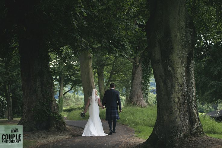 The bride & groom take a stroll in the green grounds of Tulfarris. Weddings at Tulfarris Hotel & Golf Resort photographed by Couple Photography.