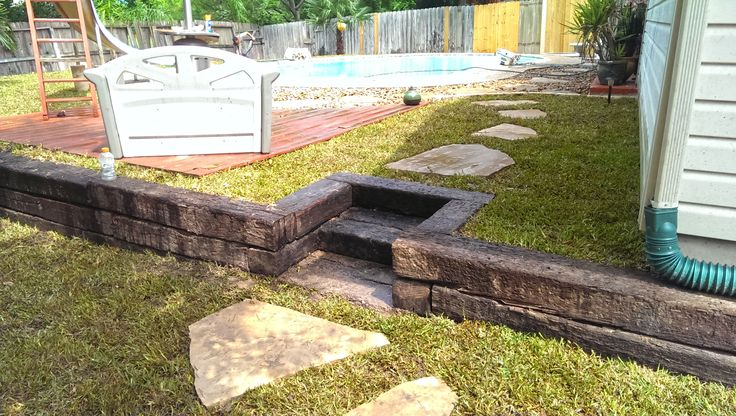 Backyard Landscape. Railroad Tie Retaining Wall w/ Built In Steps. Flagstone Walkway, and Fresh Sod.