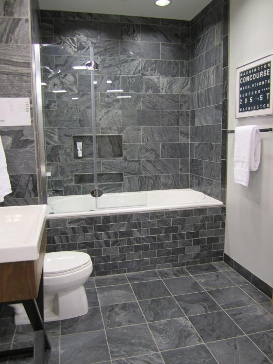 this bathroom uses the gray slate tile from the floor and into the bathtub the slate gives this bathroom a clean natural and even semi masculine look
