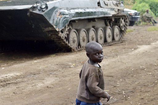 A child walks near a Democratic Republic of Congo regular army tank as soldiers fire heavy munitions nearby, in Rutshuru, on November 4, after the army recaptured the area from M23 rebels. (Junior D. Kannah/AFP/Getty Images)