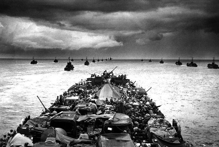 Columns of troop-packed LCIs (Landing Craft, Infantry) trail in the wake of a Coast Guard-manned LST (Landing Ship, Tank) en route to the invasion of Cape Sansapor, New Guinea in 1944