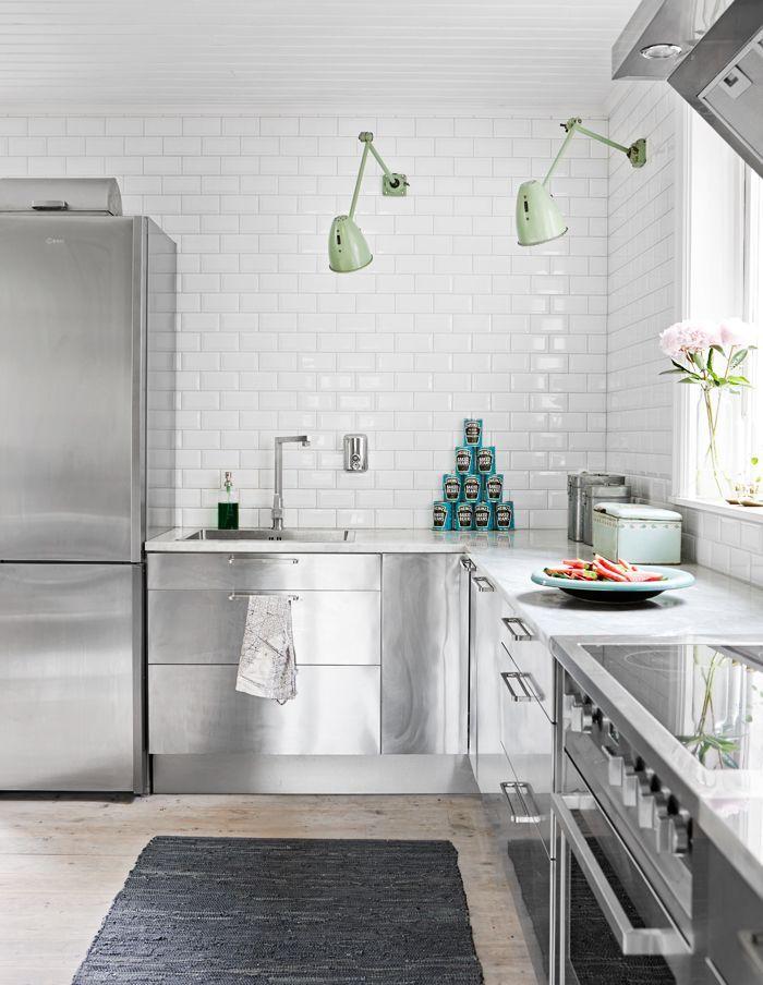 En la cocina de estilo industrial, detalles como los apliques de luz en las paredes y la alfombra gris sirven para suavizar la decoración