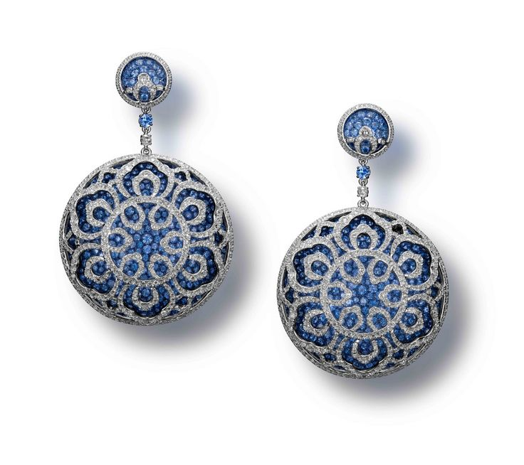 A Pair of Blue Sapphire and Diamond 'Blue and White Reverie' Earrings by Carnet. Each designed as an annular drop composed of a titanium base pavé-set with blue sapphires, overlaid with a domed openwork motif set with rose-cut diamonds, mounted in titanium and white gold, signed Carnet.