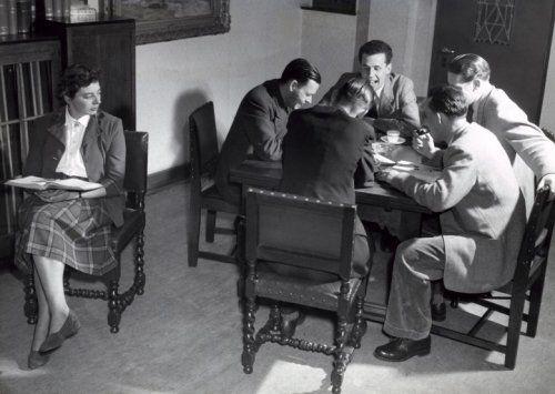 Mannen hebben plezier aan tafel terwijl een vrouw met boek opschoot jaloers of verstoord omkijkt. Haarlem, 20 maart 1952