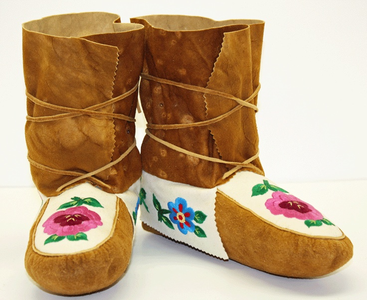 Wrap around moccasin style made by a Tlicho of Behchoko, NT, Canada. Made out of Caribou and Moose Hide. Flowers are embroidered.