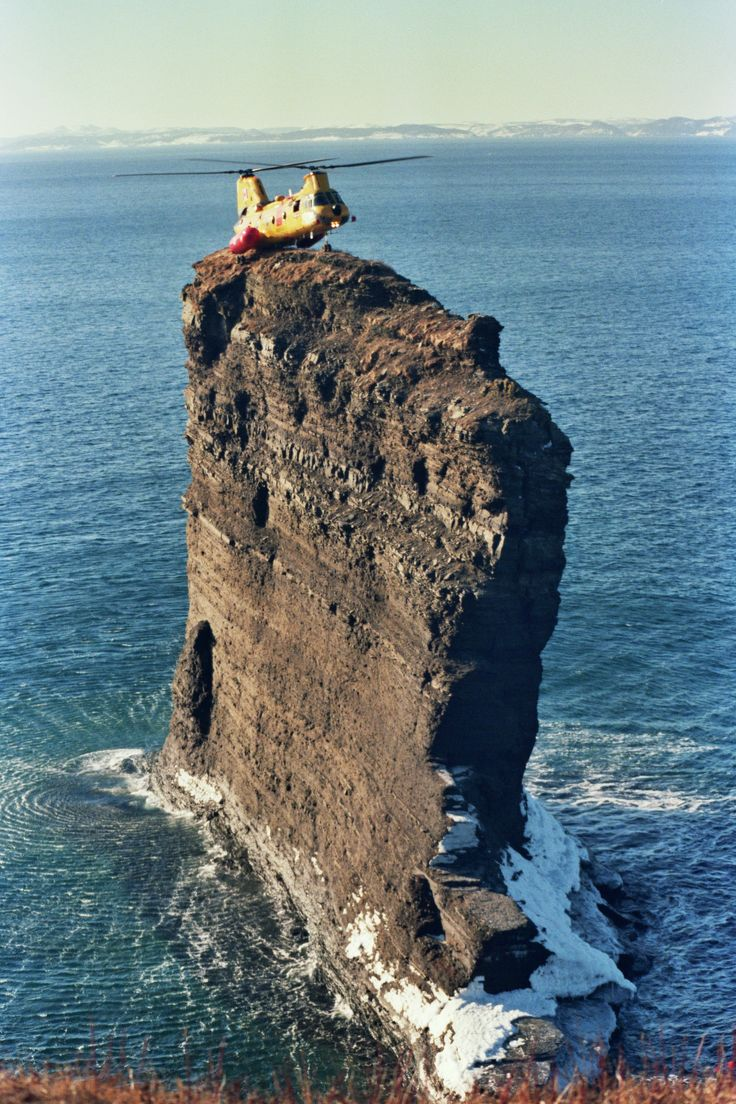 """A Canadian Forces CH-113 Labrador helicopter landing on """"The Clapper,"""" a sea stack off the tip of Bell Island (Newfoundland) in 1987."""