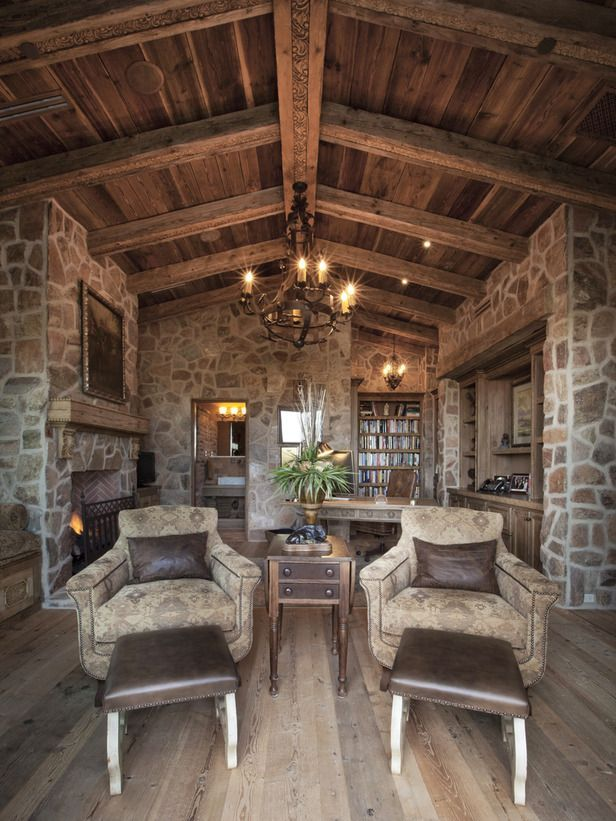 Upholstered Armchairs With Leather Pillows Face Leather Ottomans In This  Dramatic Home Office. Aged Wooden Beams And Stone Walls Complete The Rustic  ...