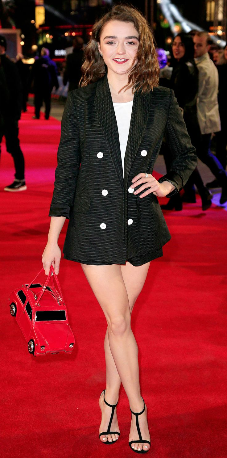 Maisie Williams completely charmed at the UK premiere of The Revenant in a sleek, menswear-inspired shorts suit that she playfully styled with a car-shaped novelty purse and T-strap sandals.