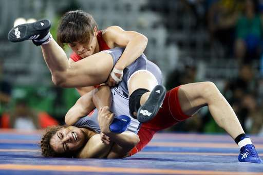 Japan's Kaori Icho, red, competes against Tunisia's Marwa Amri during the women's 58-kg freestyle wrestling competition at the 2016 Summer Olympics in Rio de Janeiro, Brazil, Wednesday, Aug. 17, 2016. (AP Photo/Markus Schreiber)