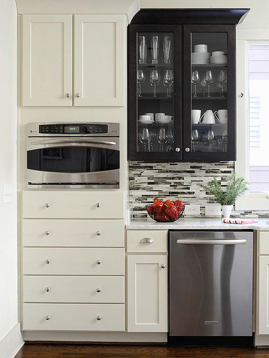Add drama to your kitchen by contrasting light-color cabinetry with a dark-stained cabinet.