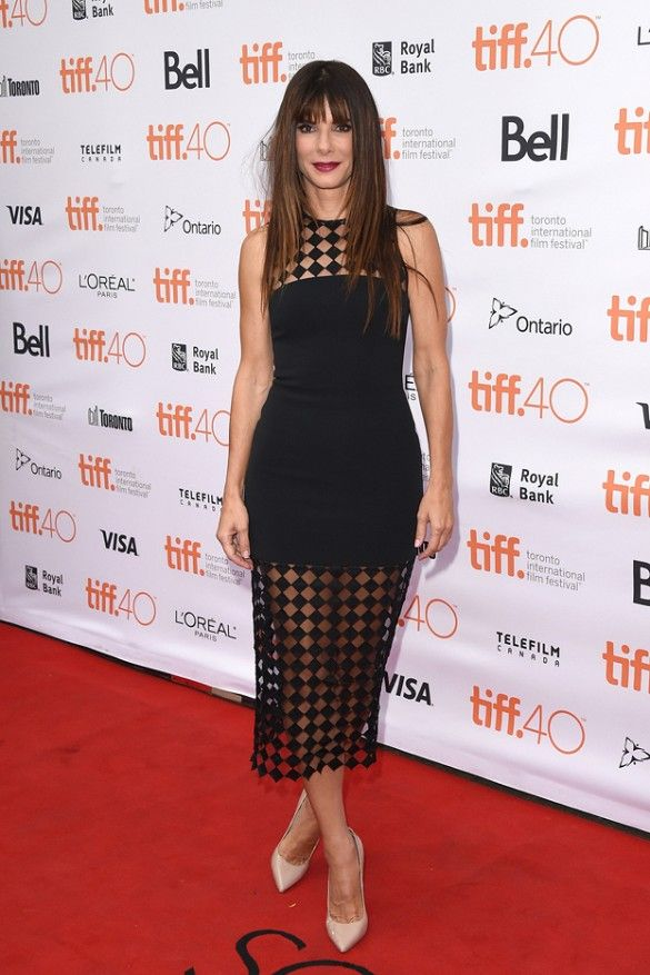 Sandra Bullock wears a black dress with sheer paneling and nude pointed-toe pumps