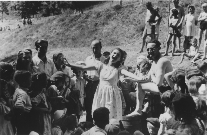 Singing in the DP Camp, 1946.  This image of an unknown teenager singing in a DP Camp (where they held Holocaust survivors for a while) is just so beautiful. There's something incredible at seeing an image of so many survivors in one picture, smiling, and with this girl in the center looking absolutely joyous.