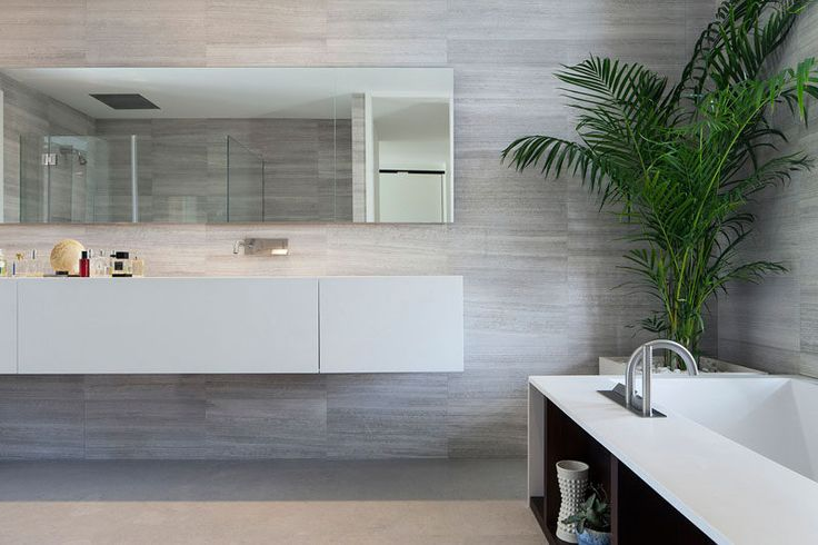 In this master bathroom, the mirror matches the length of the floating vanity. Soft gray tones have been paired with white cabinetry for a contemporary look.