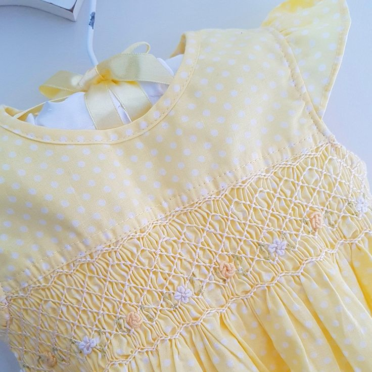 I am in love with this sweet little  dress! Elegantly hand smocked and adorned with hand embroidered flowers.
